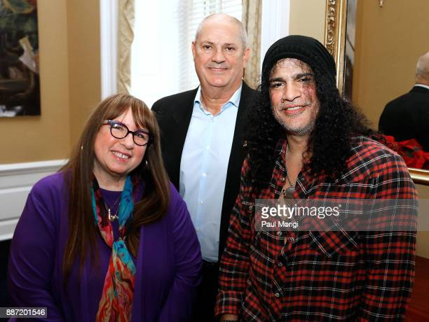 Diane Blagman of The Recording Academy Producer Mike Clink and Slash of Guns N' Roses pose for a photo prior to the SLASH Holiday Reception hosted by...
