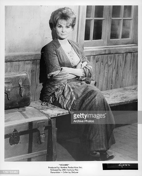 Diane Cilento sitting on a bench in a scene from the film 'Hombre' 1967