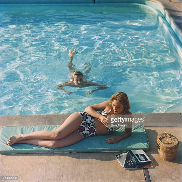 Diane Fletcher relaxing by a pool at the Kona Kai Club on Shelter Island, San Diego, California, 1960. She is wearing a two-piece swimsuit by Marie...