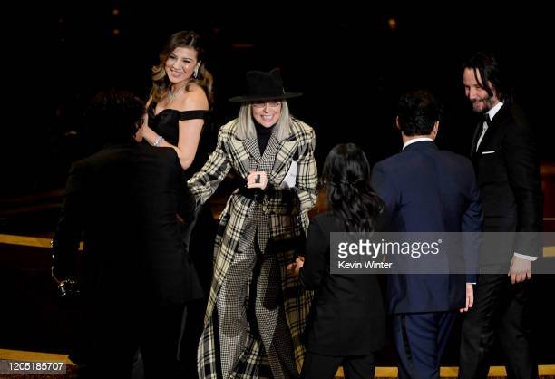 Diane Keaton and Keanu Reeves walk onstage with Bong Joonho interpreter Sharon Choi and Han Jinwon after they accepted the Writing Original...