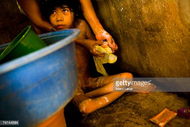 Diane Liwanag is bathed by her mother May 30 2006 inside her family's home at the Mauaque resettlement site in Pampanga Philippines Diane is...