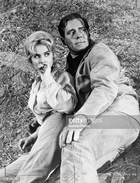Diane McBain and Philip Carey laying on the ground together in a scene from the film 'Black Gold' 1962