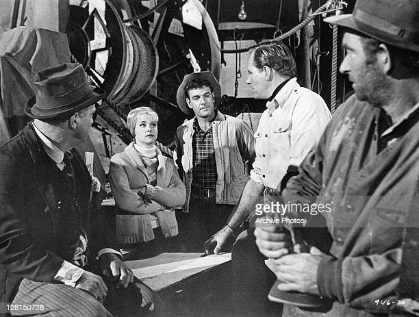 Diane McBain and Philip Carey listen to plan from group of men in a scene from the film 'Black Gold' 1962