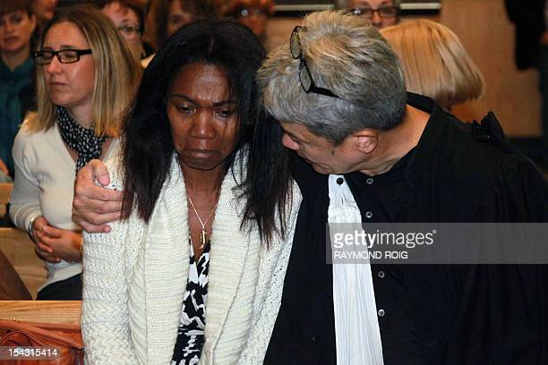 Diane Mistler a Madagascan woman who allegedly tricked one of her many lovers into killing her husband with a fishing harpoon is comforted by her...
