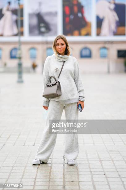 Diane Perreau wears a gray wool turtleneck oversized pullover, a Chanel logo bejeweled brooch, a Hermes Kelly brown leather crossbody bag, wool...