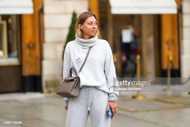 Diane Perreau wears a gray wool turtleneck oversized pullover, a Chanel logo bejeweled brooch, a Hermes Kelly brown leather crossbody bag, wool...