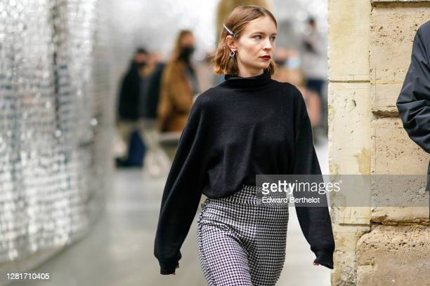 Diane Rouxel wears a black oversized turtleneck pullover with large sleeves, black and white houndstooth pattern pants, outside Paco Rabanne, during...