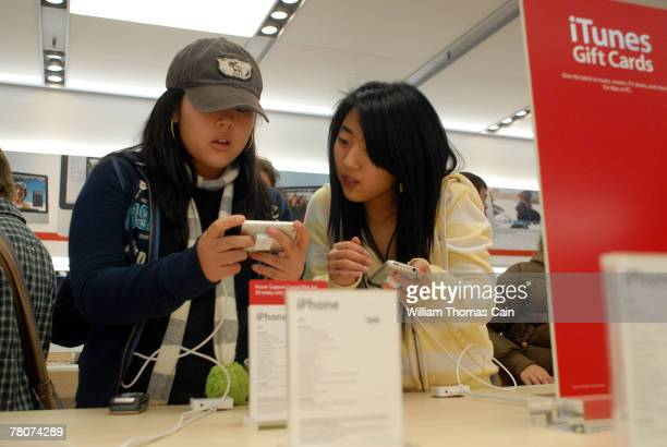 Diane Song and Jennifer Song of Hockessin Delaware look at an iPhone in the Apple store at the King of Prussia Mall November 23 2007 in King of...