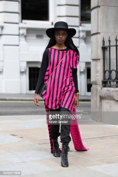 Diane Umuhoza wears Gianco Handmade outfit and Liu Jo bag during London Fashion Week September 2018 on September 14 2018 in London England