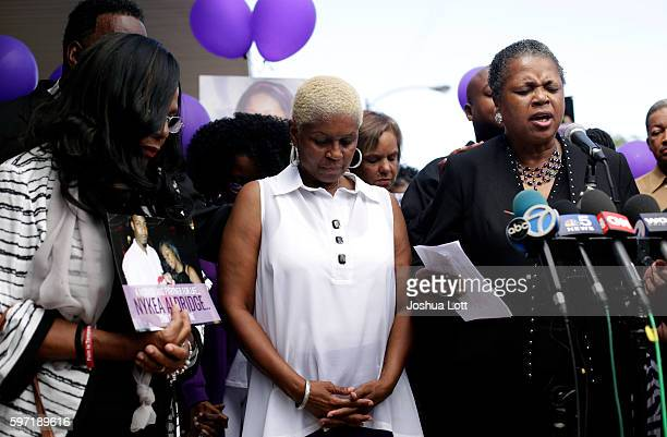 Diann Aldridge center the mother of Nykea Aldridge bows her head during a vigil for her daughter as her sister Jolinda Wade right leads a prayer...
