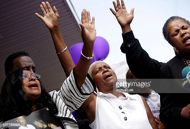 Diann Aldridge center the mother of Nykea Aldridge holds her hand in the air during a vigil for her daughter as her sister Jolinda Wade right leads a...