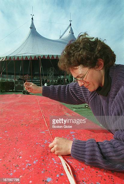 Dianna Yoxall stitches up a ripped seam in the crash mat that tumblers at the Big Apple Circus will use Behind her workers erect the tent that will...