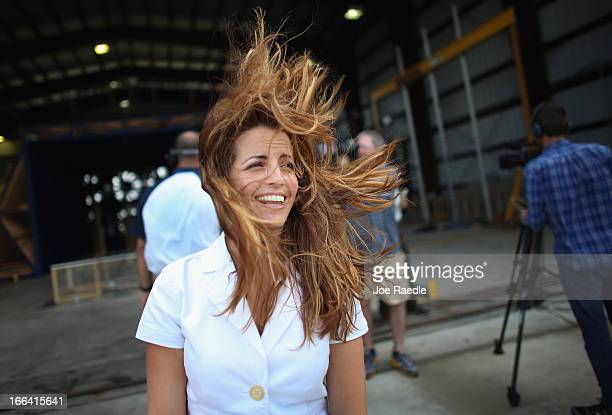 Dianne Fernandez, a broadcast specialist with Florida International University, hair blown around as she stands near twelve fans, that create what is...