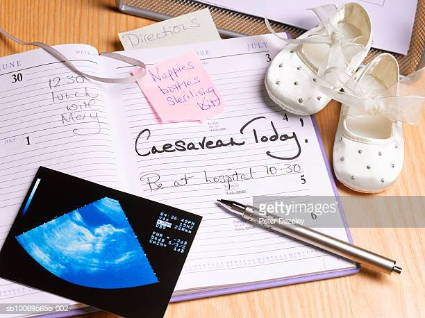 Diary and pen on desk with baby booties, high angle view
