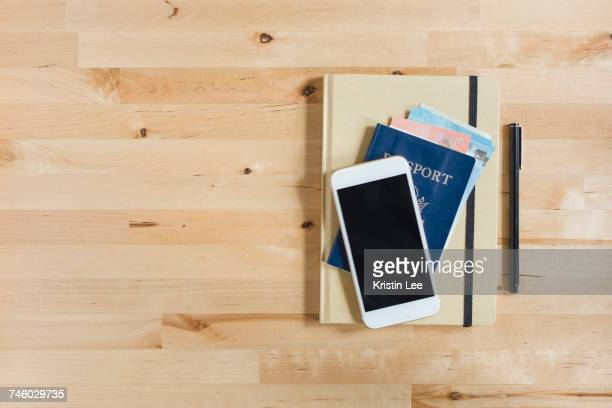 diary, passport with paper currency, smart phone and pen on wooden table - passeport photos et images de collection
