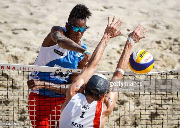 Diaz Nivaldo of Cuba spikes the ball against Robin Seidl of Austria during the Men's Main draw elimination match between Cuba and Austria on August...