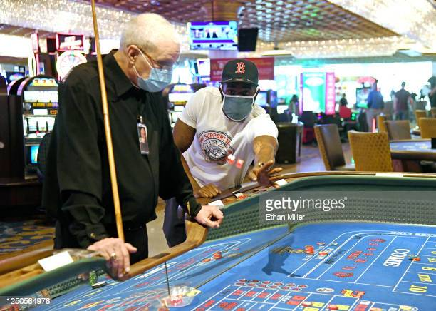 Dice dealer Phil Moffett looks on as John Moore of California rolls the dice at a craps table at the Westgate Las Vegas Resort & Casino after the...