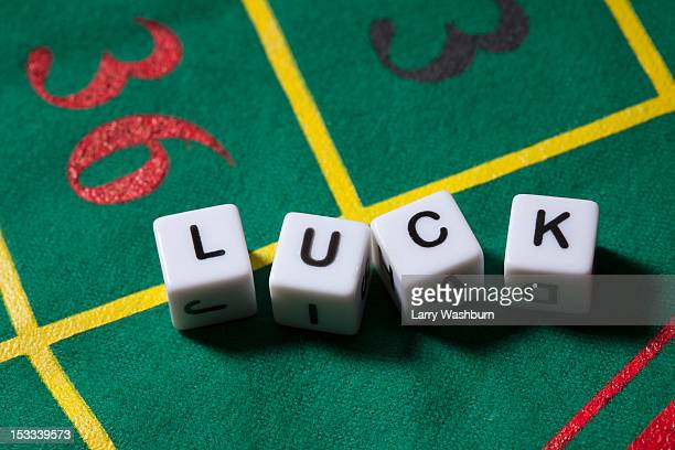 Dice on a gambling table spelling the word LUCK