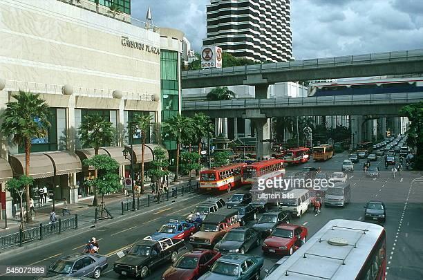 """Dichter Verkehr auf der Ratchadamri Road; links das """"Gaysorn Plaza"""" Einkaufzentrum; über der Strasse die Hochbahn """"Skytrain""""- August 2000"""