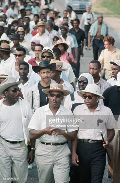 Dick Gregory and James Meredith walk alongside Martin Luther King Jr on a rural road during the March Against Fear