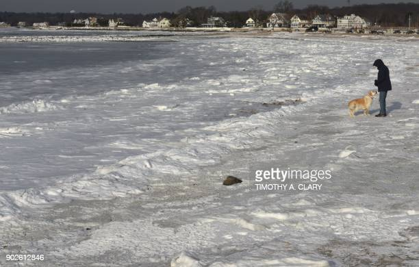Dick Healy of Wesport Connecticut walks his dog along the frozen Long Island Sound at Compo Beach in Westport Connecticut January 8 2018 The...