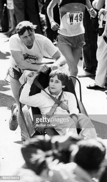 Dick Hoyt holds the hands of Rick Hoyt as they run along Beacon Street during the Boston Marathon April 19 1982