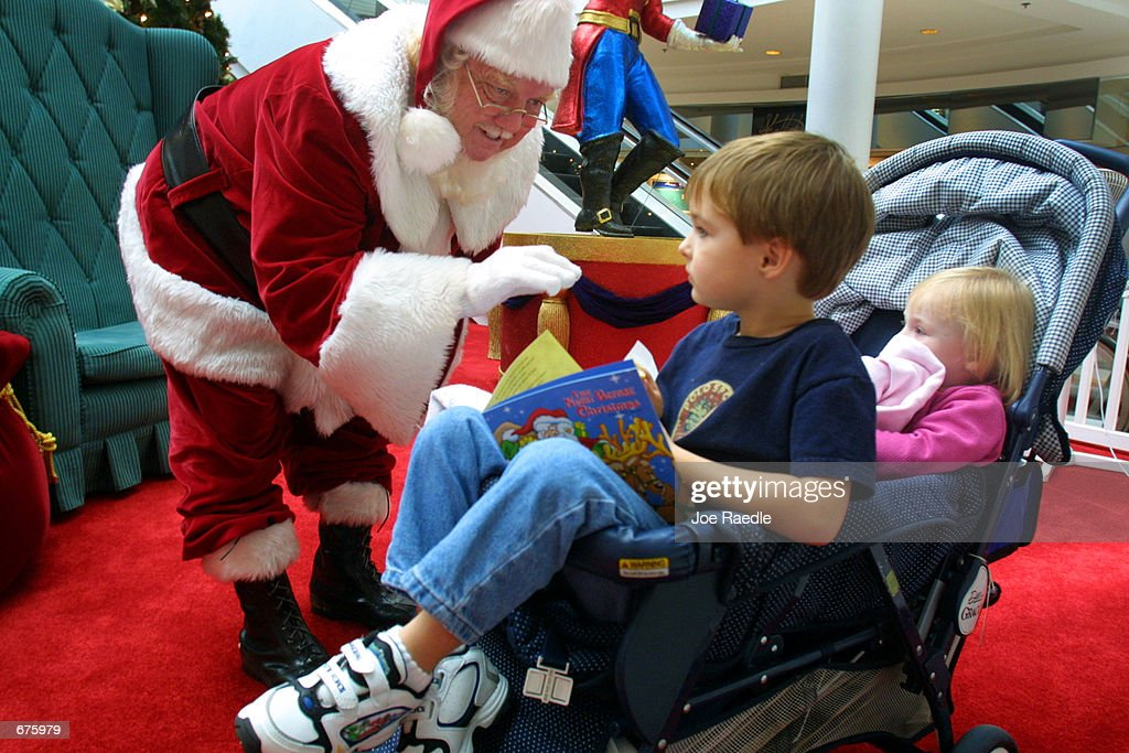 Dick Johnson dressed as Santa Claus speaks to Christian Pelkey and
