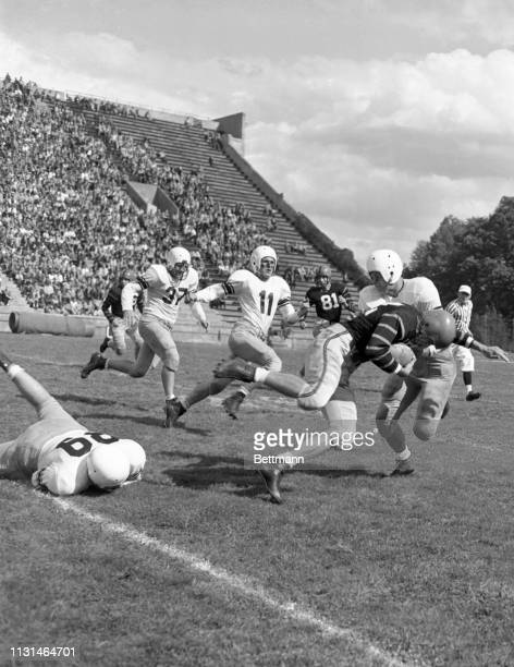 Dick Kazmaier Princeton left halfback cuts through the Lafayette line and into the open before Jay Barclay Lafayette left halfback pulls him down...