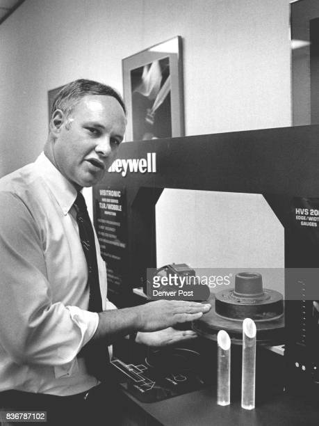 Dick Lane Gen Mgr of Honeywell Visitronics with an edge gauge which can tell width of pieces of metal Can tell when assembly line machines make...