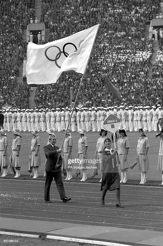 Dick Palmer, Great Britain's Chef de Mission and sole representative in the opening ceremony, carries the Olympic flag around the Olympic Stadium