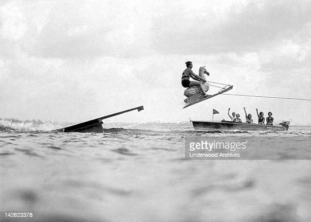 Dick Pope famous aquaplane champion plays 'horsey' in front of an admiring boatload of beauties on Manhasset Bay Long Island New York late 1920s