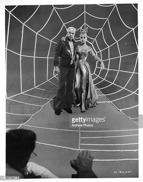 Dick Powell and Anne Francis standing in front of a man made spider web in a scene from the film 'Susan Slept Here' 1954