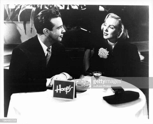 Dick Powell sits at a table with Marilyn Monroe in a scene from the film 'Right Cross' 1950