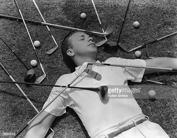 Dick Powell the American singer actor and director lying apparently asleep amongst golf equipment Original Publication People Disc HK0437
