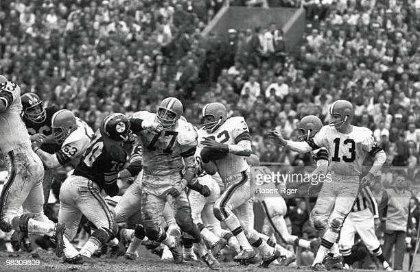 Dick Schafrath of the Cleveland Browns blocks for Jim Brown as Frank Ryan looks on during a circa 1960s game against the Pittsburgh Steelers