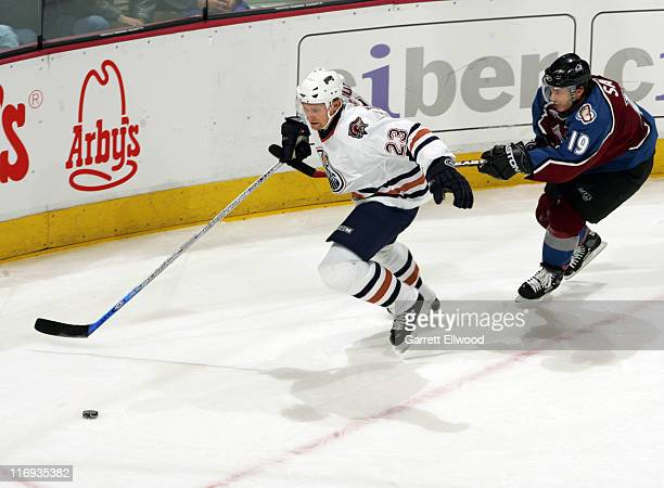 Dick Tarnstrom of the Edmonton Oilers is held by Joe Sakic of the Colorado Avalanche during the game on March 26, 2006 at Pepsi Center in Denver,...
