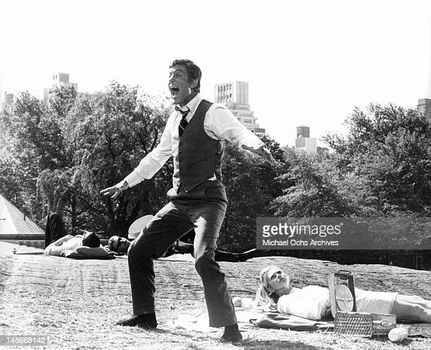 Dick Van Dyke standing in a park yelling dressed in a full suit without his jacket in a scene from the film 'Some Kind Of Nut' 1969