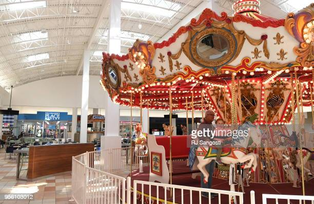 Dick Weatherbee babysits his granddaughter Alex Bacci as they ride the carousel at Colorado Mills Mall one year after a massive hail storm damages...