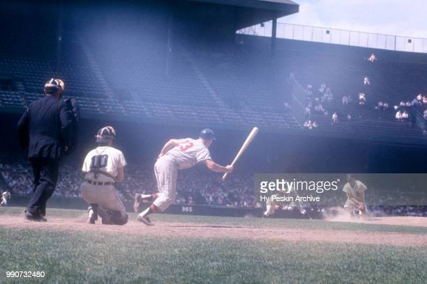 Dick Williams of the Kansas City Athletics swings runs towards first base as catcher Red Wilson and umpire Larry Napp look on during an MLB game on...