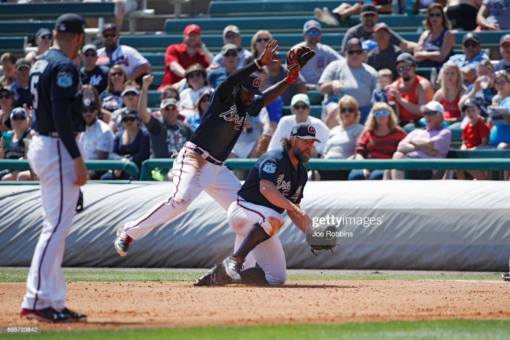 R.A. Dickey #19 of the Atlanta Braves collides with Brandon Phillips #4 after a botched play at first base in the fourth inning of a Grapefruit League spring training game against the Miami Marlins at Champion Stadium on March 20, 2017 in Lake Buena Vista, Florida. The Marlins defeated the Braves 9-3.