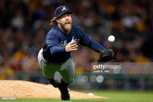 A Dickey of the Atlanta Braves makes a diving play to get the out in the sixth inning against the Pittsburgh Pirates at PNC Park on April 8 2017 in...