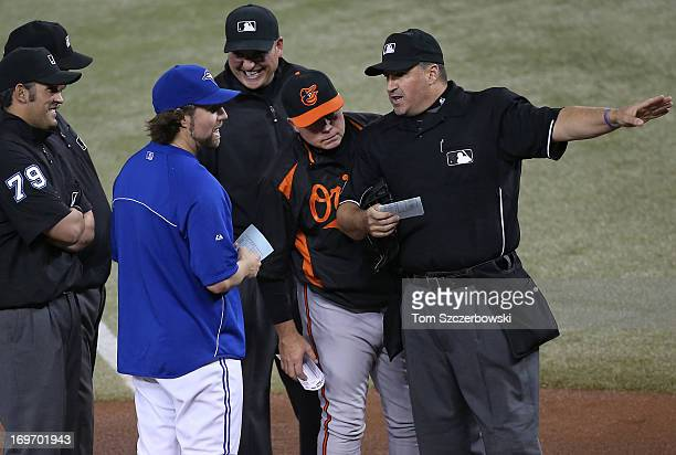 A Dickey of the Toronto Blue Jays and manager Buck Showalter of the Baltimore Orioles deliver the lineups to home plate umpire Tony Randazzo and...