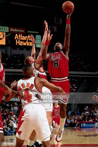 Dickey Simpkins of the Chicago Bulls attempts a layup against Spud Webb of the Atlanta Hawks during a 1996 NBA game at the OMNI Coliseum in Atlanta...