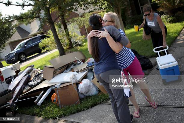 Dickinson resident hugs a friend who came to help her remove possessions damaged by flooding brought on by Hurricane Harvey September 1 2017 in...