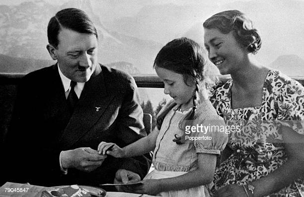 1930's German Chancellor Adolf Hitler in relaxed mood having just signed his autograph for a small girl as her mother looks on The picture was taken...