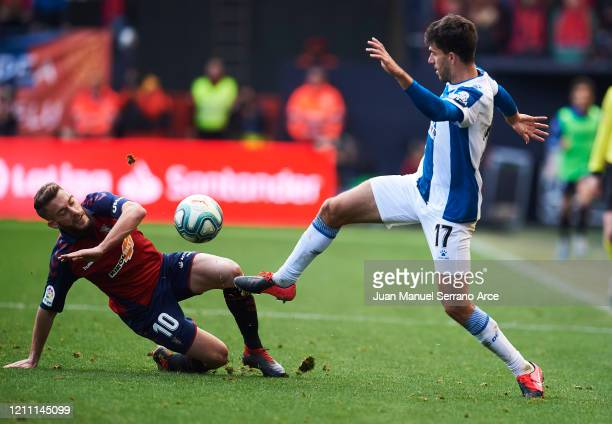 Didac Vila of RCD Espanyol duels for the ball with Roberto Torres of CA Osasuna during the Liga match between CA Osasuna and RCD Espanyol at El Sadar...