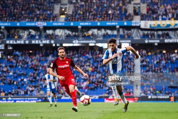 Didac Vila of RCD Espanyol runs for the ball under pressure from Franco Vazquez of Sevilla FC during the La Liga match between RCD Espanyol and...