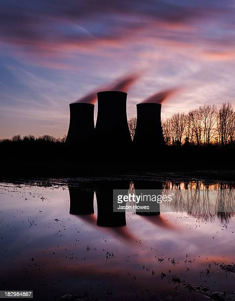 Didcot power station UK, steaming cooling towers at sunset, reflected in a pool of water