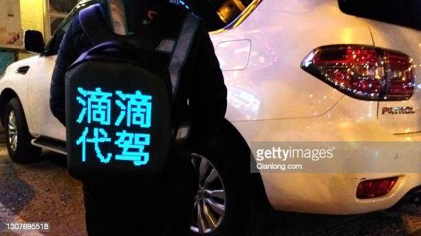 Didi Chuxing's designated driver carrying an illuminated backpack stands on the street on March 17, 2021 in Beijing, China.