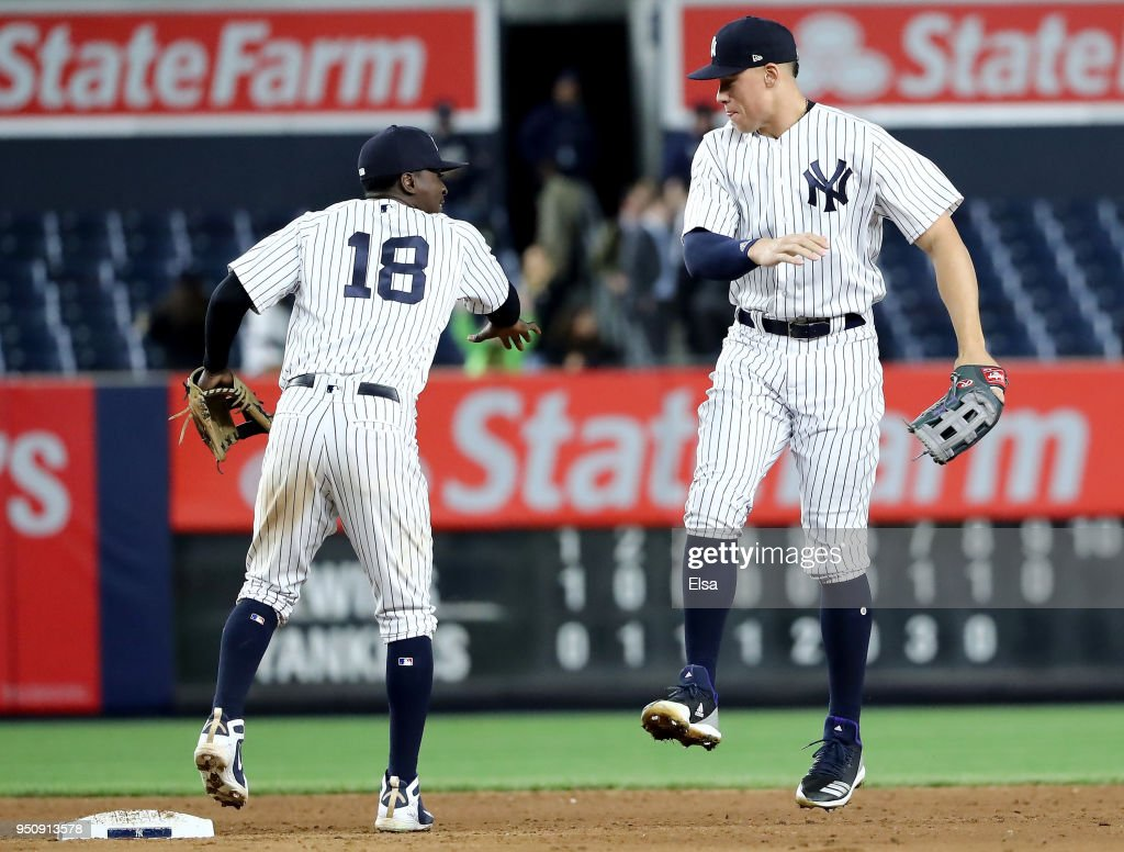 Didi Gregorius #18 and Aaron Judge #99 of the New York Yankees celebrate the 8-3 win over the Minnesota Twins at Yankee Stadium on April 24, 2018 in the Bronx borough of New York City.